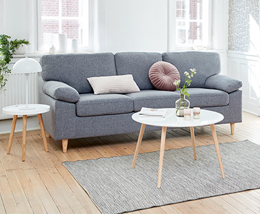 3-personers sofa i lysegrå i lys stue med rundt sofabord