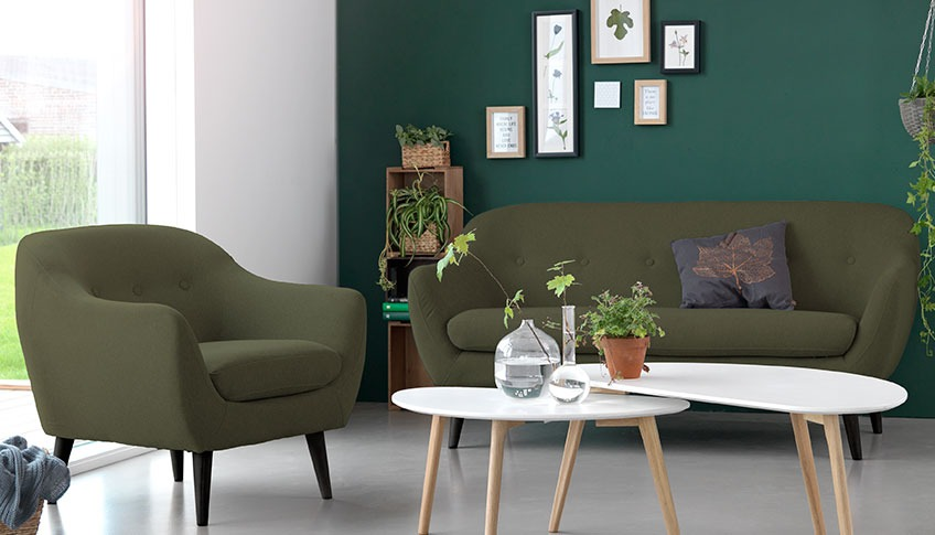 A living room with a green velvet sofa and armchair a two coffee tables