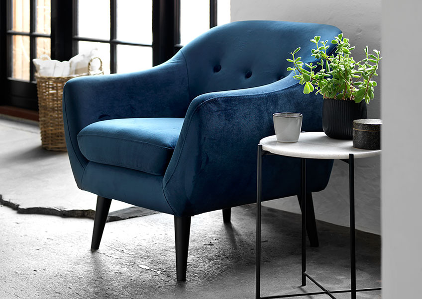 A living room with a blue velvet armchair and a coffee table