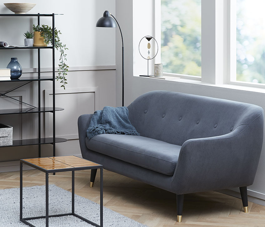 A living room with a small sofa that leaves space for an armchair for reading